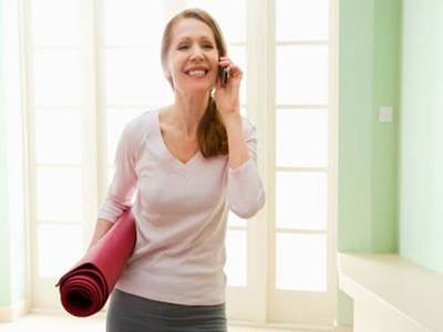 Woman with yoga mat and cell phone