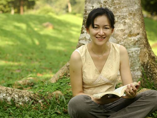 Asian woman reading under a tree.