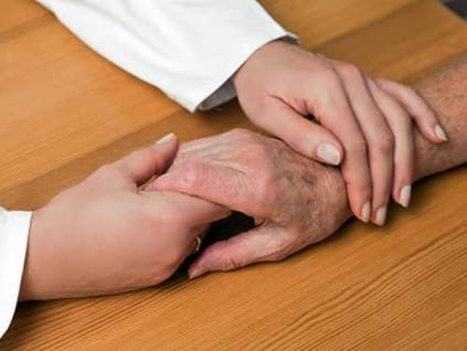 Wood desk, holding hands with elderly relative.