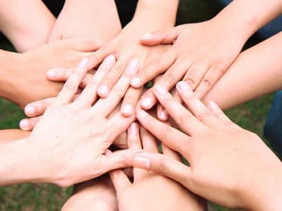 Hands in a circle on top of each other, community
