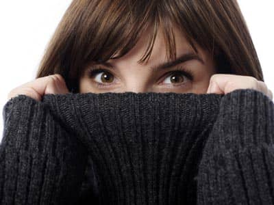 A woman's eyes peeking above a turtleneck