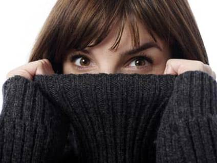 A woman's eyes peeking above a turtleneck