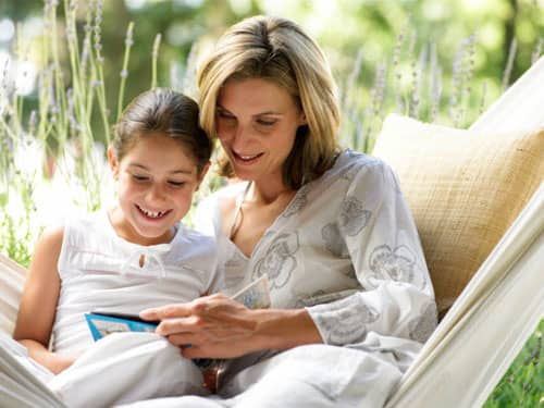 Mother and daughter reading on a hammock
