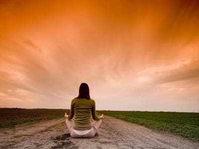 Woman meditate sunset
