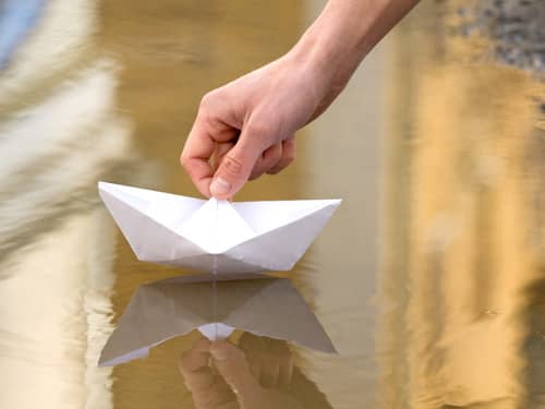 Hand placing paper boat in water