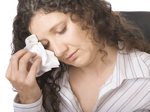Woman dries tears with tissue