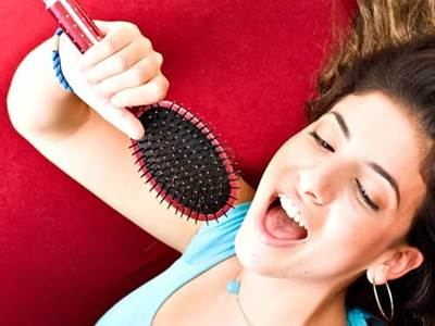 Girl singing into a brush