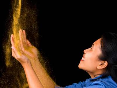 Gold dust pouring onto woman's hands