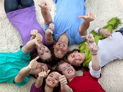 Kids lying down in the sand with thumbs up
