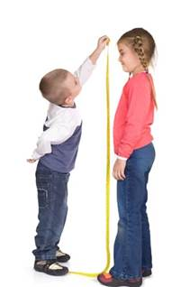 Boy measuring height of girl