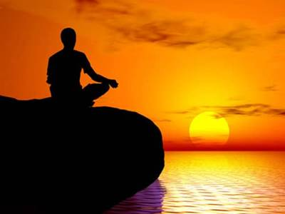 Man meditating at sunset