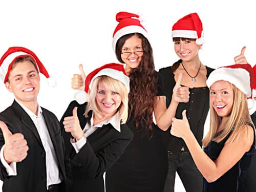 Business people in santa hats, thumbs up
