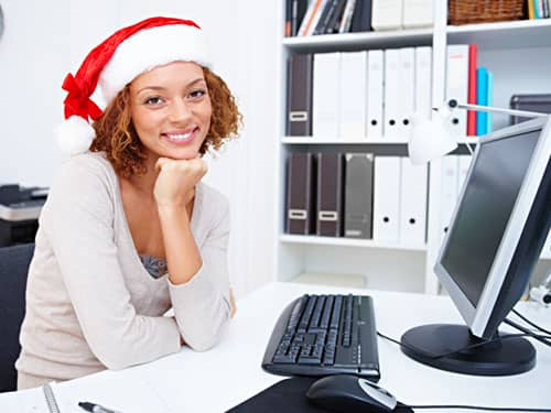 Santa hat woman in front of computer