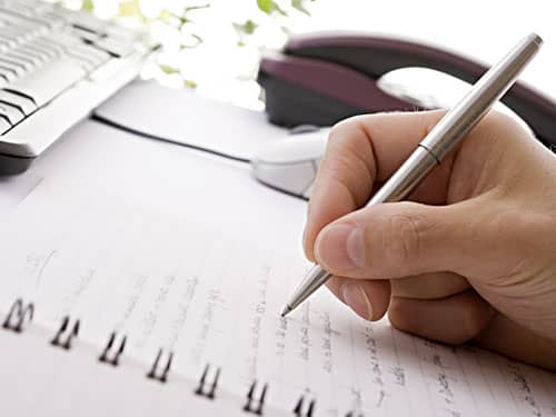 Hand writing in notebook with pen