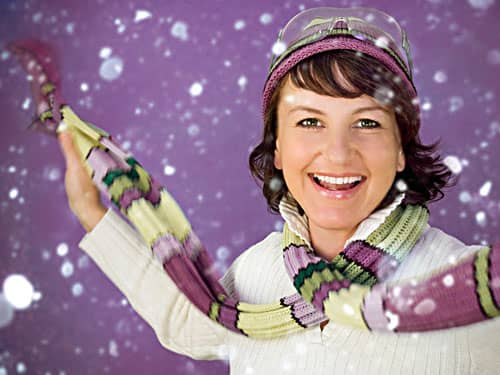 Happy woman in snow on violet