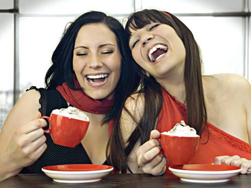 Girlfriends laughing over coffee