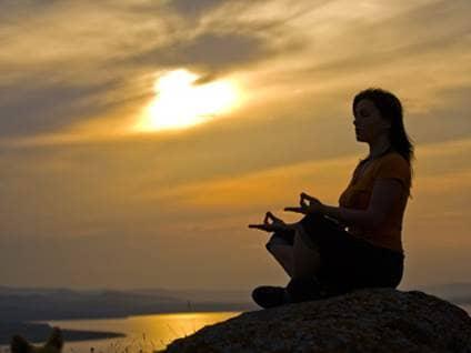 Meditating against an orange sky.