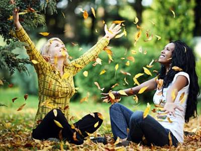 Two women playing in the leaves