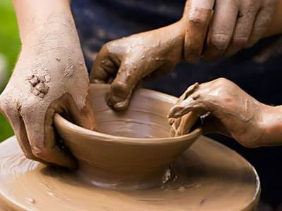 Two sets of hands on potters wheel