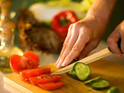 Woman's hand cutting vegetable food with knife