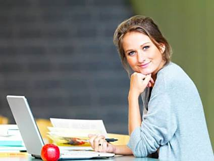 Woman studying in a library on laptop