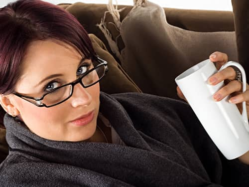 A woman relaxing in a comfortable robe on the couch, with tea