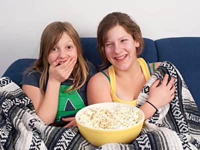 Two girls watching a movie at home on a couch