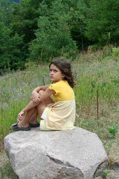 girl sitting on rock