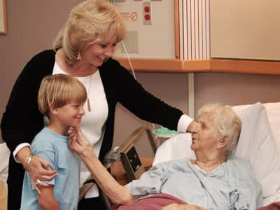 Family mother son visiting elderly grandmother in hospital bed