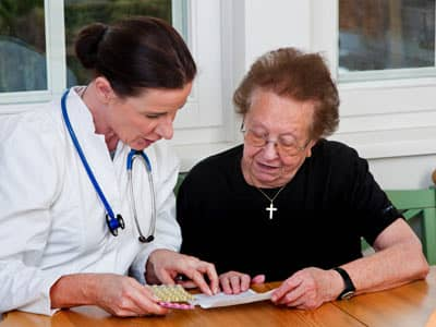 A nurse discussing health options with an elderly christian woman