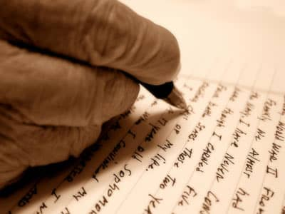 An elderly hand correcting a letter with a pen