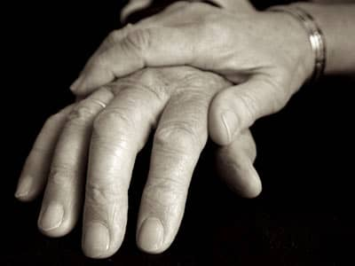 Black and white hand comforting an elderly person's hand