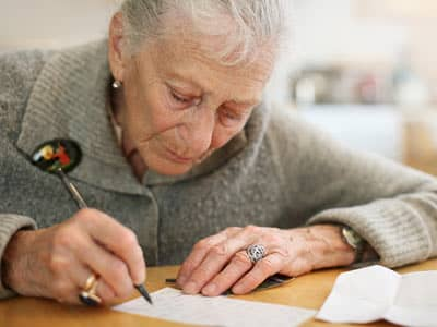 An elderly woman writing