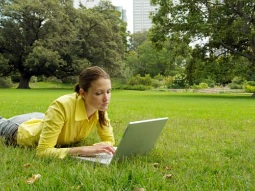 Girl relaxing outside with laptop