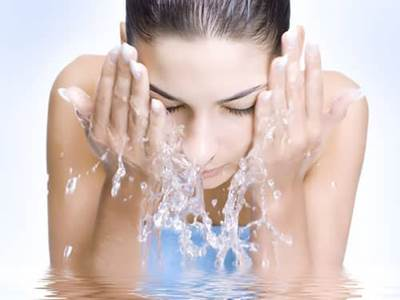 Woman splashing water on her face