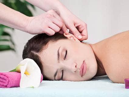 Woman having ear massaged