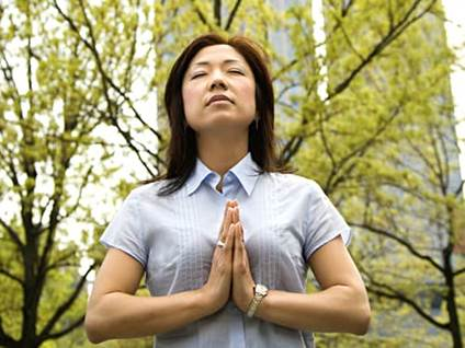Asian woman meditating in the wood
