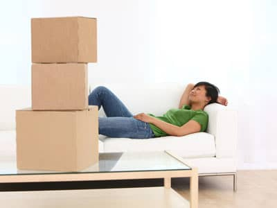 Woman resting on a couch, stacked boxes on a table.
