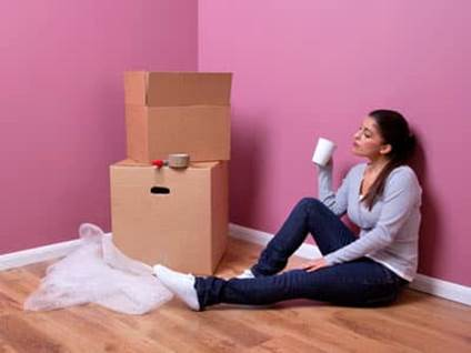 Woman taking a break and drinking while packing to move.