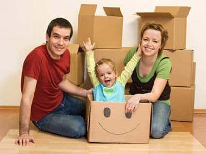 A mother and father packing for a move, with a smiling child in a box.