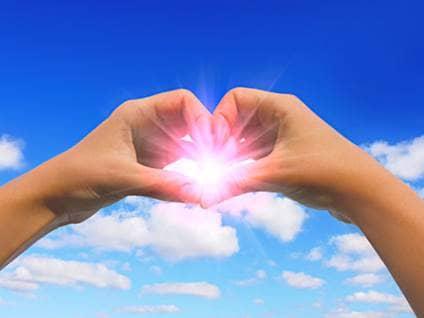 Heart hands around soft pink light