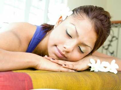 A woman in navy blue resting with closed eyes on a bed, flowers in her brown hair.