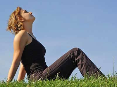 A woman sitting on a green grass field, looking up into a clear blue sky.