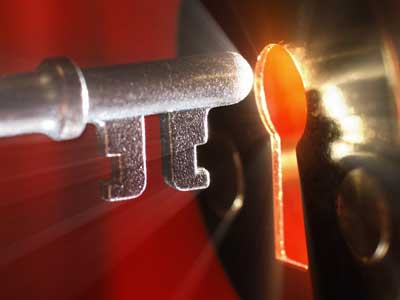 A grey key unlocking a shining lock.