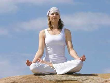 A woman in white clothes and a bandana meditating on a rock against the blue sky.