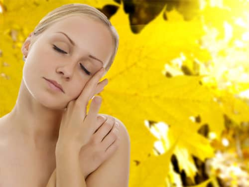Blonde woman set against yellow leaf