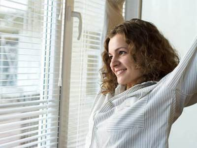 Woman waking up looking out window