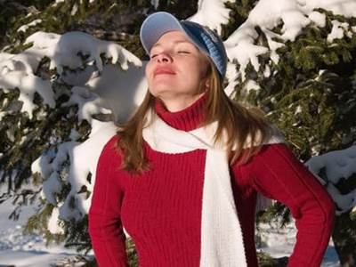 Woman in red taking deep breath in snowy forest
