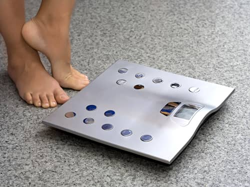 Woman's feet next to metal scale