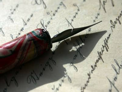 Old-fashioned pen against a letter